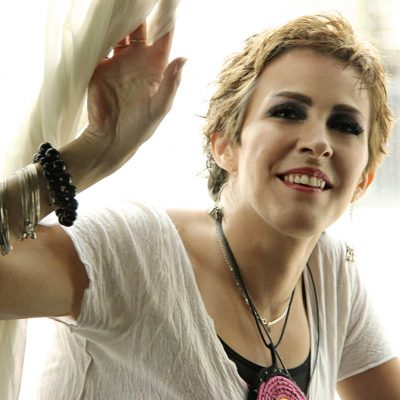 Syrian Analytic Cubism and Abstract painter Leen Batal wearing a white T-shirt and a black and red necklace and raising her right hand
